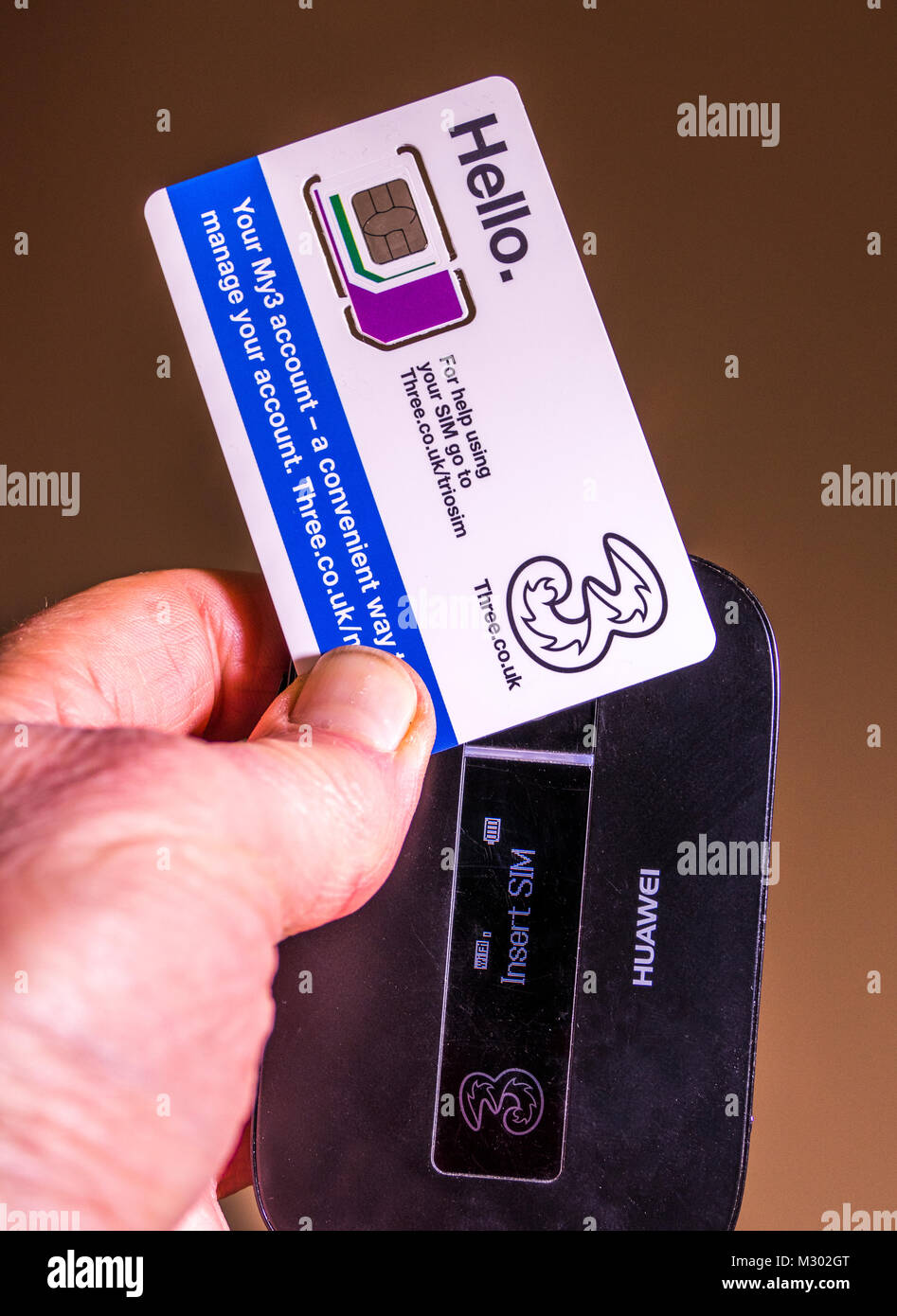 Man's hand holding a Three data Trio (three sized) SIM card, to be inserted into a Huawei portable wifi router, - Stock Image