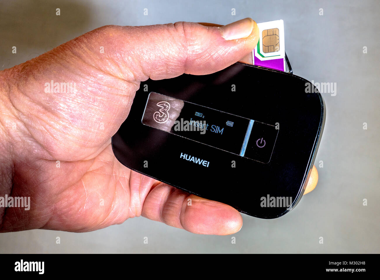 Man's hand holding Three data Trio (three sized) SIM card, being inserted into a Huawei portable wifi router, - Stock Image