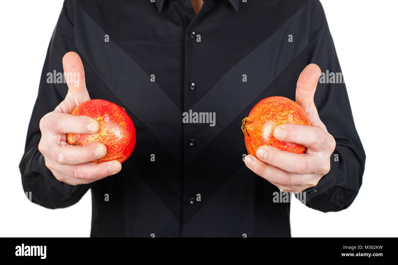 Close up picture of man in black holding ripe pomegranate, high antioxidant fruit - Stock Image