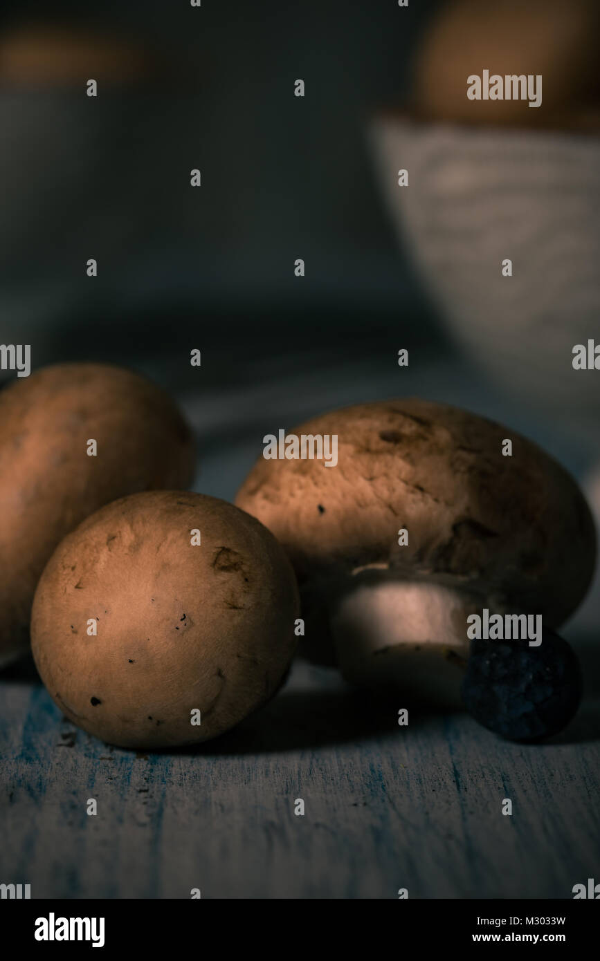 Vertical photo with several brown edible mushrooms. Raw champignons are spilled on blue vintage wooden board with - Stock Image