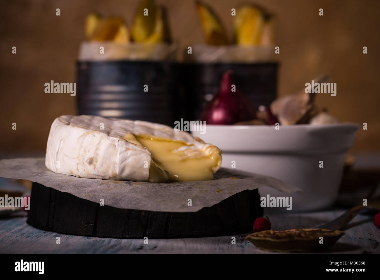 Horizontal photo with whole grilled camambert cheese. Small triangle piece is cut off and melted cheese is floating - Stock Image