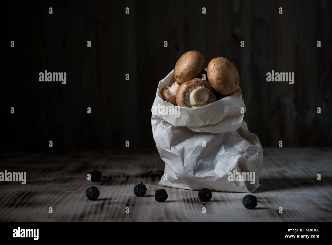 Horizontal photo with several brown edible mushrooms. Raw champignons are in white paper bag. Bag is on vintage - Stock Image