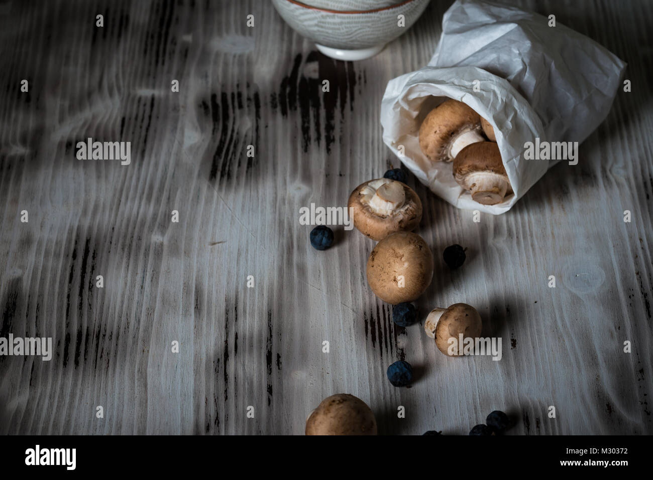 Horizontal photo with several brown edible mushrooms. Raw champignons are spilled from white paper bag on vintage - Stock Image