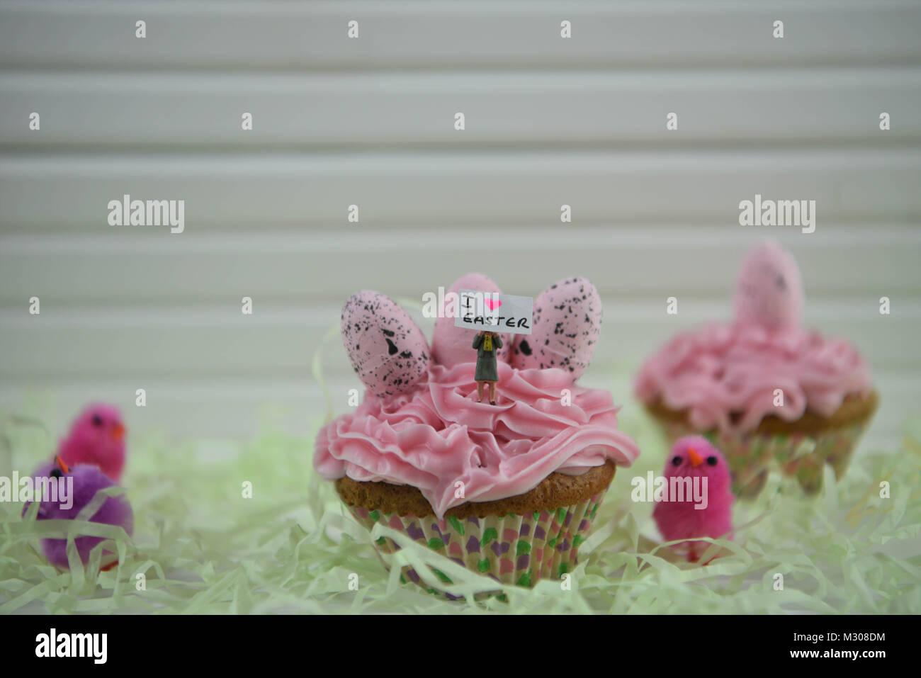 Easter time pink cupcake with egg decorations and miniature person figurine on top with a sign of I love Easter Stock Photo