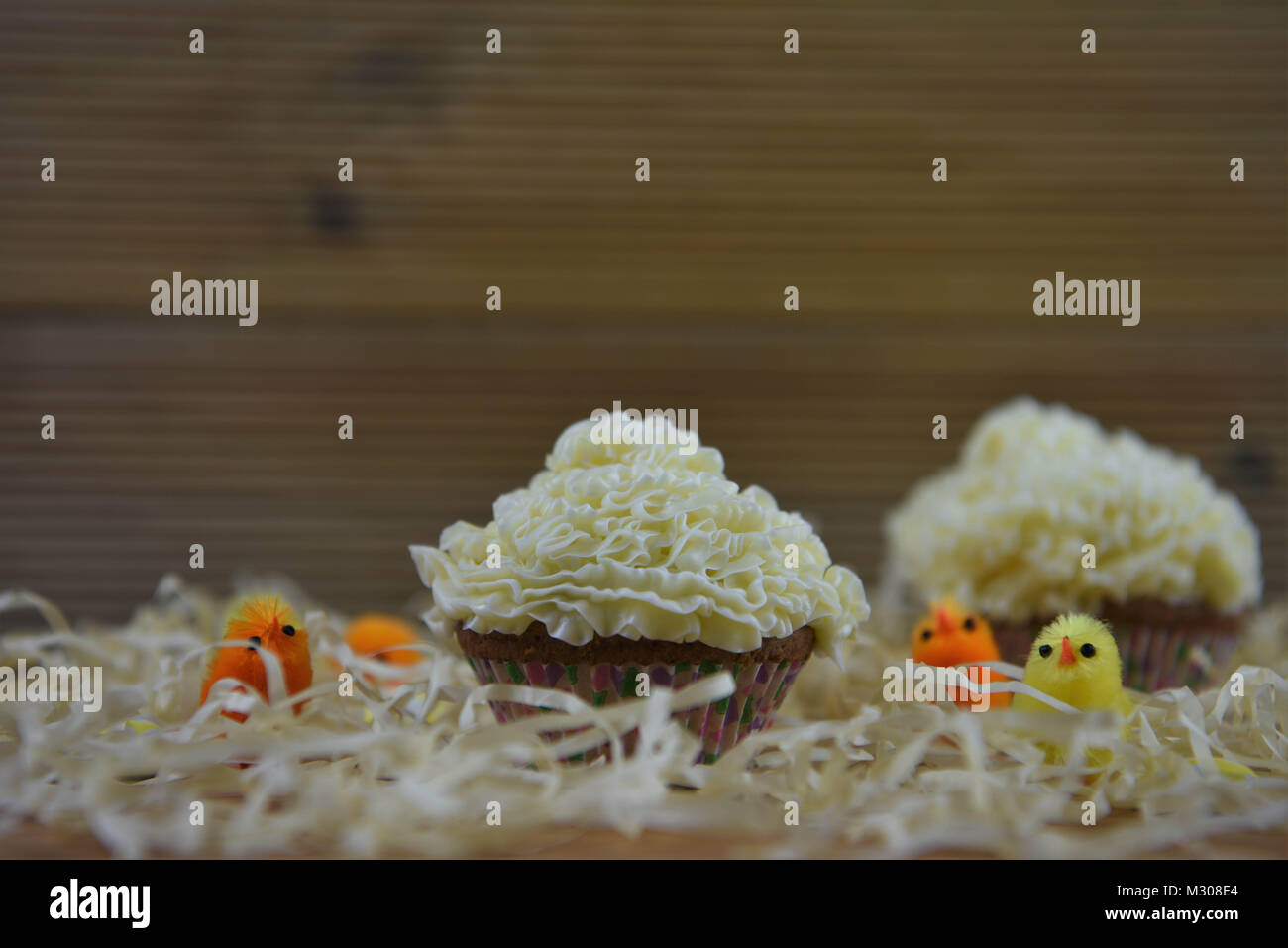 cute Easter time table with cupcake and on rustic wood with straw and fluffy chick decorations - Stock Image