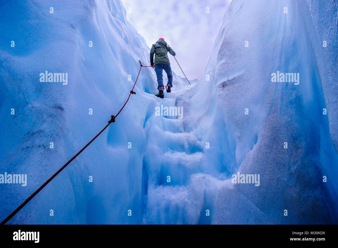 Woman walking steps out of a ice cave in Fox Glacier, South Island, New Zealand Stock Photo