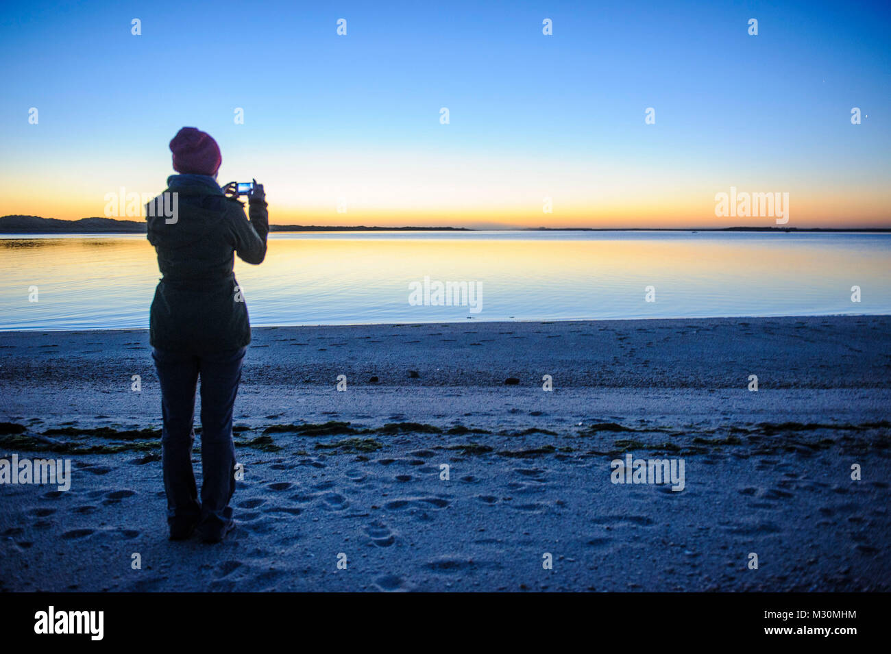 Woman photographing the stunning light over the flat ocean, the Catlins, South Island, New Zealand - Stock Image