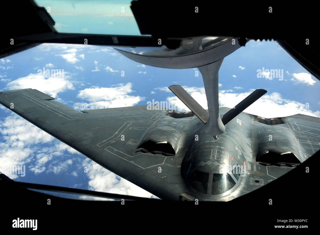 A U.S. Air Force B-2 Spirit Bomber from the 509th Bomb Wing, flies up to a KC-135 Stratotanker refueling aircraft - Stock Image