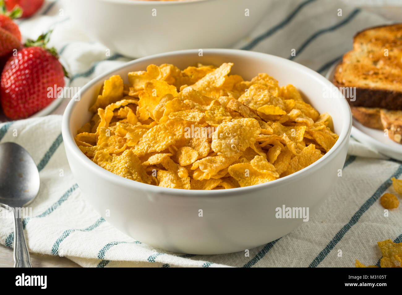 Healthy Corn Flakes with Milk for Breakfast with Fruit - Stock Image