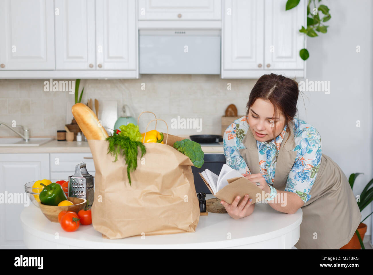 Young housewife with recipes book in the kitchen - Stock Image