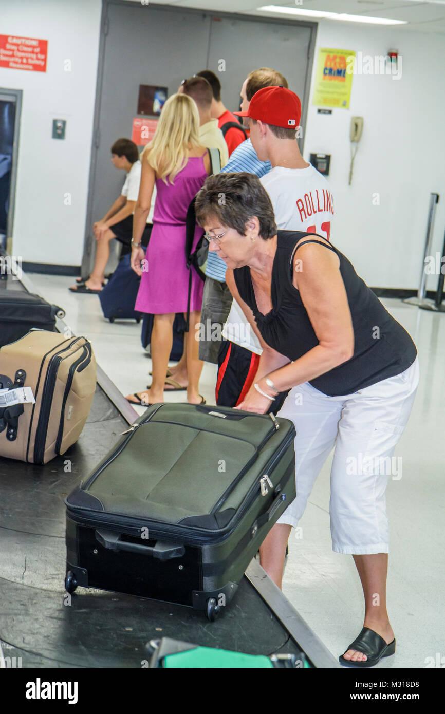 Miami Florida MIA Miami International Airport luggage claim passenger bag baggage carousel flight arrival woman - Stock Image