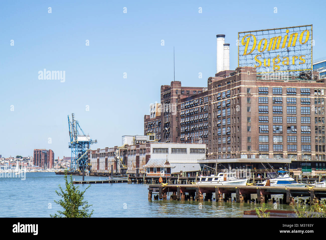Baltimore Maryland Patapsco River port waterfront Domino Sugar sugarcane refining plant sign smokestack dock business - Stock Image