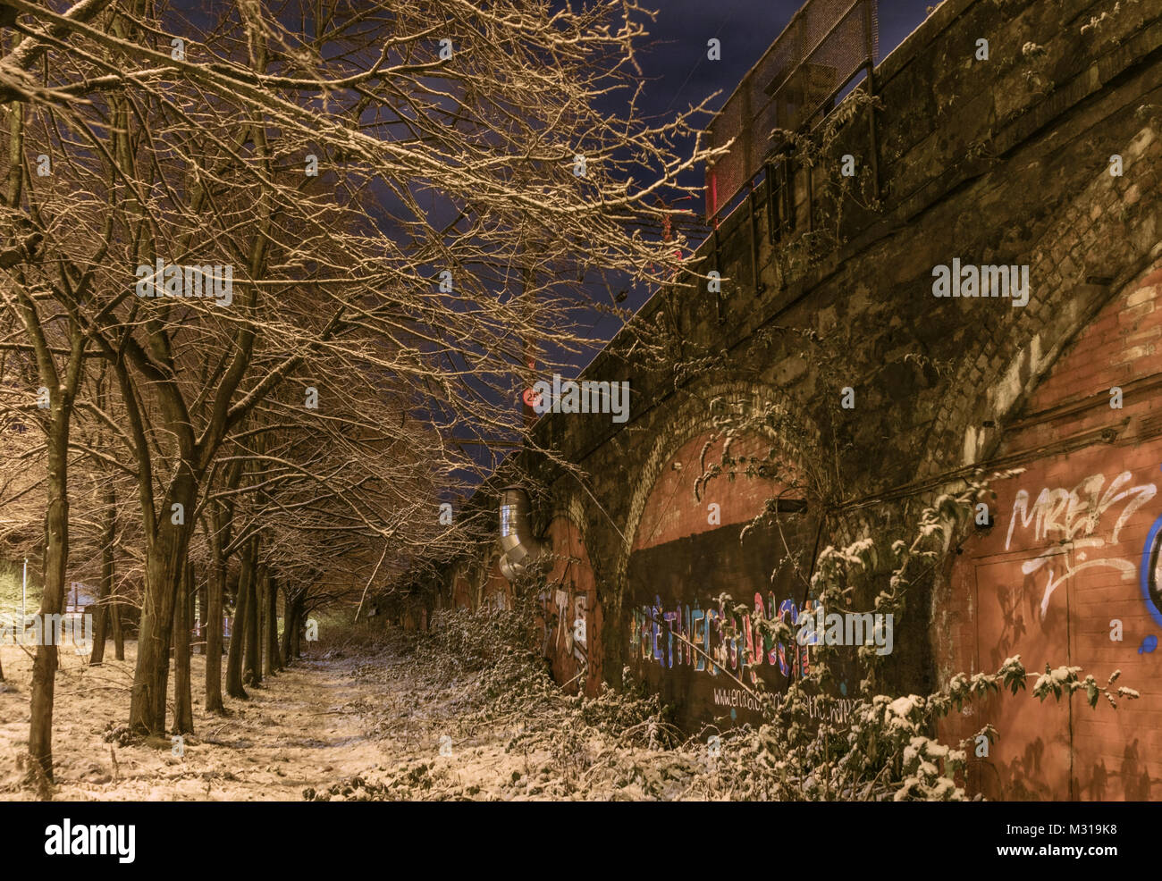 A snow covered line of trees beside railway arches becomes a dramatic landscape at night in Glasgow, Scotland, UK. - Stock Image