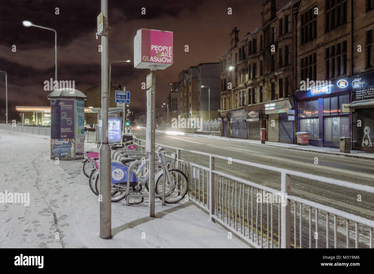 Public bicycle hire station at night after a fall of snow in Glasgow,Scotland,UK. - Stock Image