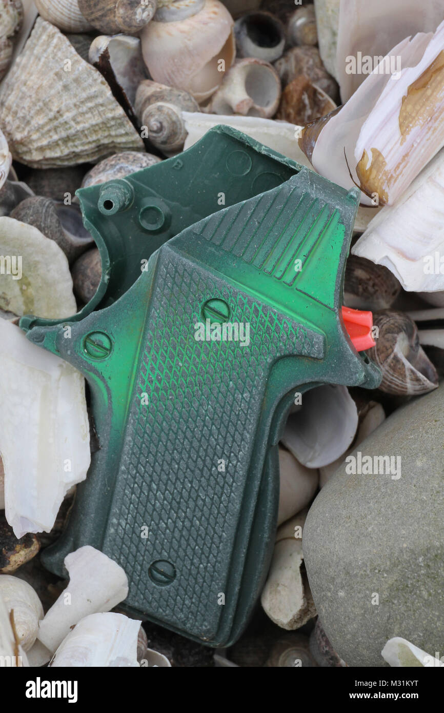 Plastic in the sea. Part of a plastic toy gun lying on shells on a UK beach.. - Stock Image
