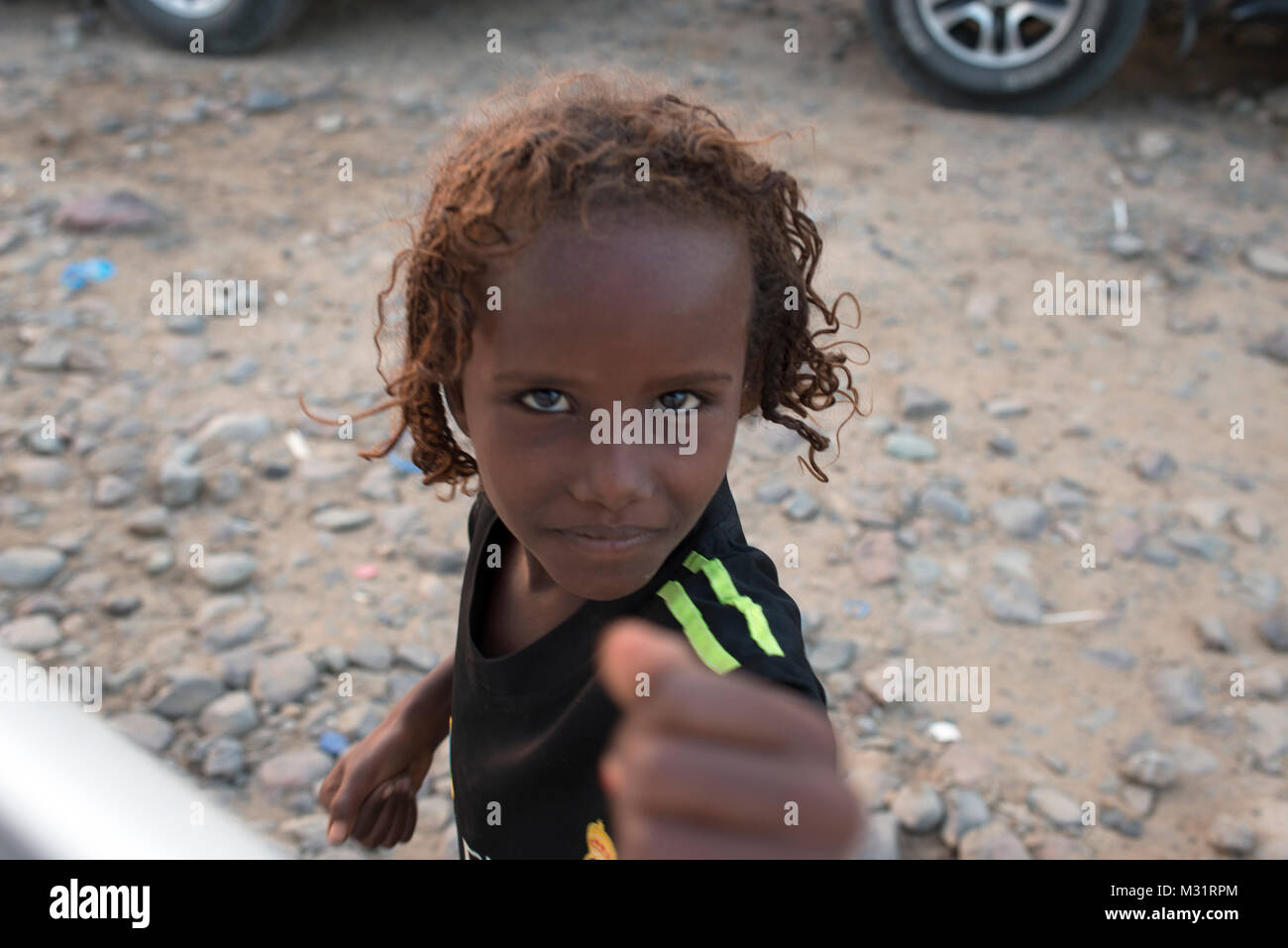 A young Afar girl pretending to punch a tourist who has no pen for her. Hamed Ale, Danakil Depression, Ethiopia. - Stock Image