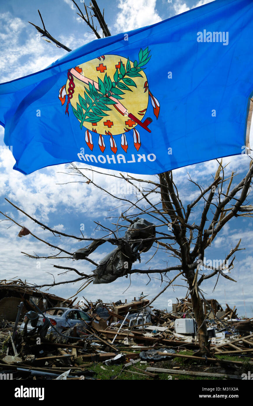 An Oklahoma State flag flies from a mangled tree in a Moore
