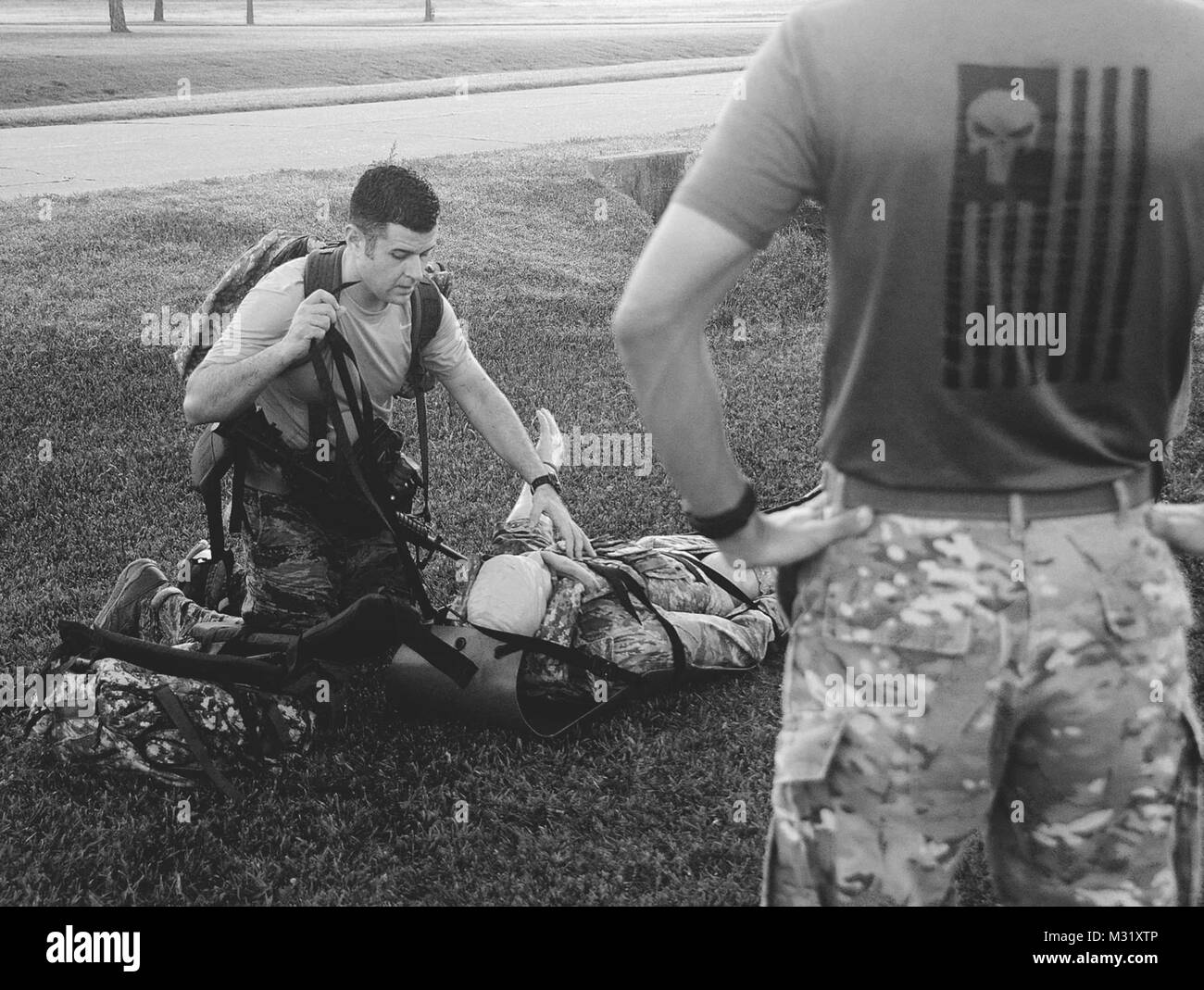 Air Force Staff Sgt. Alejandro Gomez works to securely attach a 175 pound mannequin to a Skedco litter in order - Stock Image