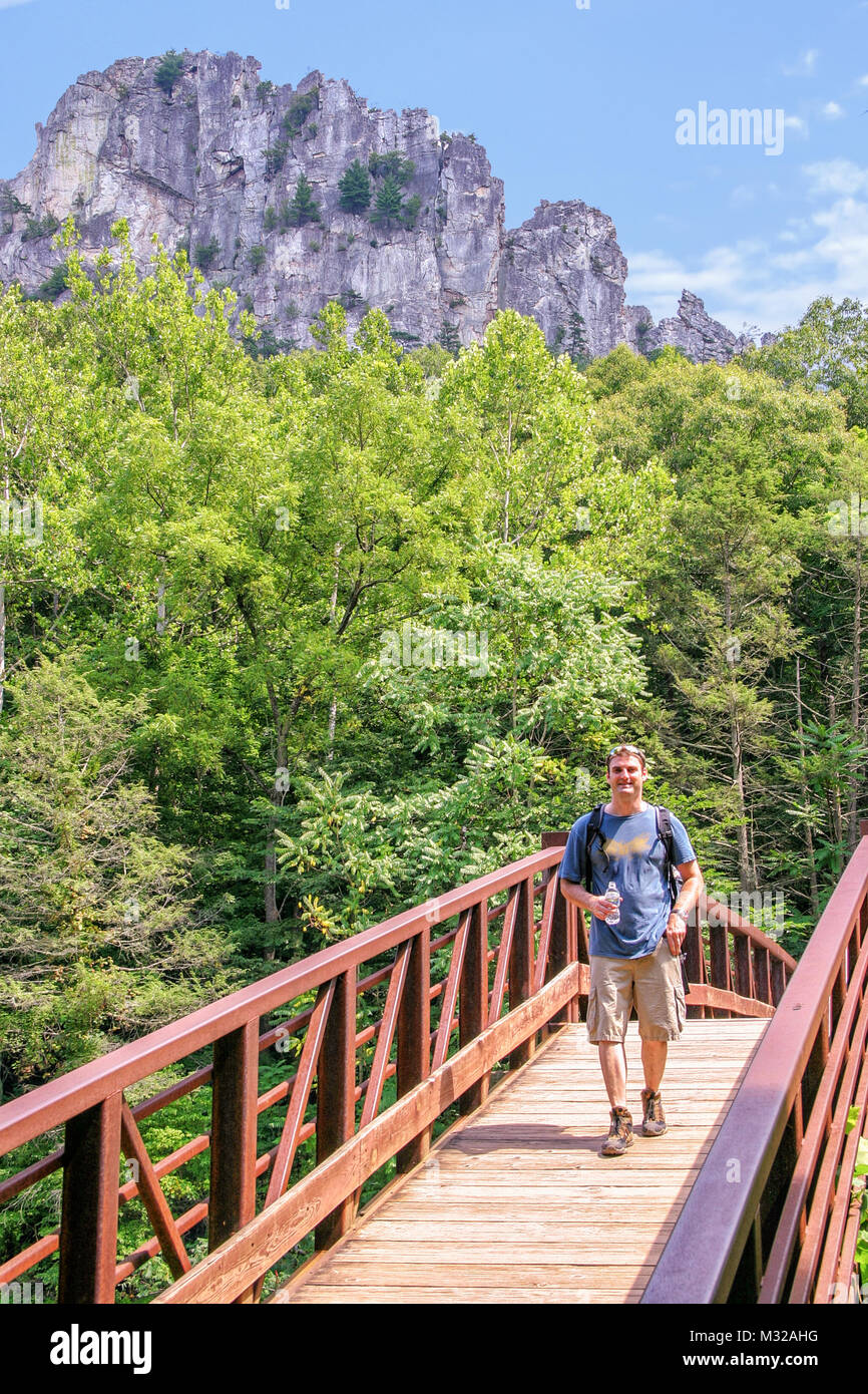 Hiker crossing a bridge at Spruce Knob National Recreation Area. The highest point in West Virginia is at the summit Stock Photo