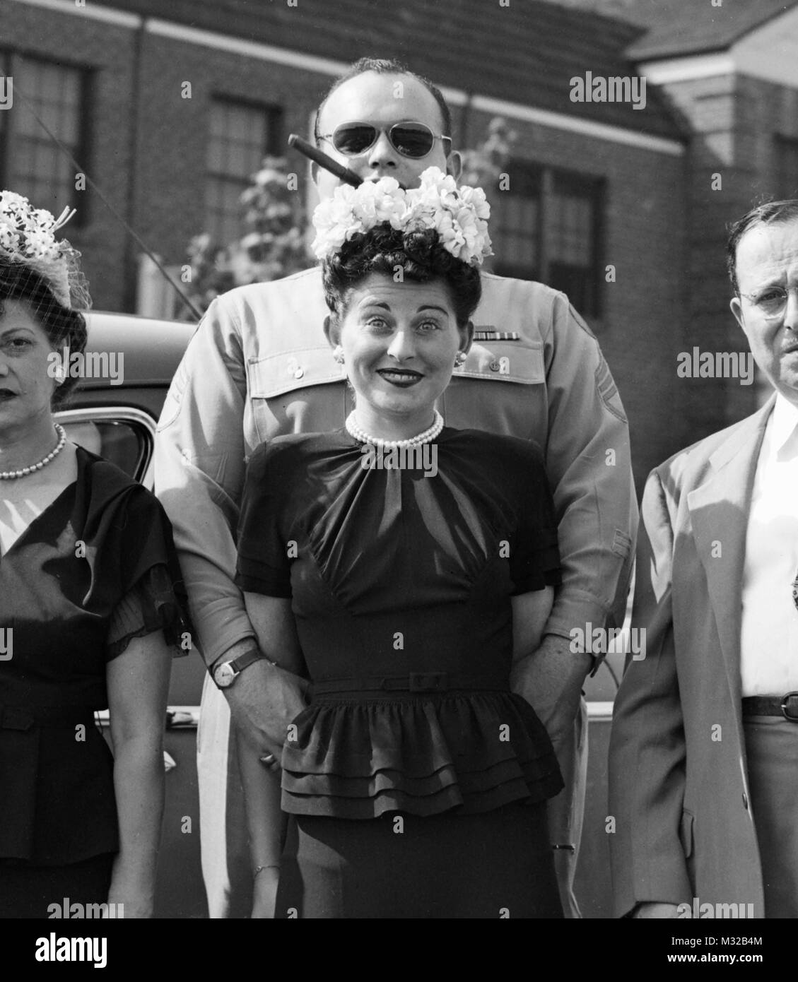 US serviceman and his girl have a goofy pose while standing with the parents for a photography, ,ca. 1944. - Stock Image