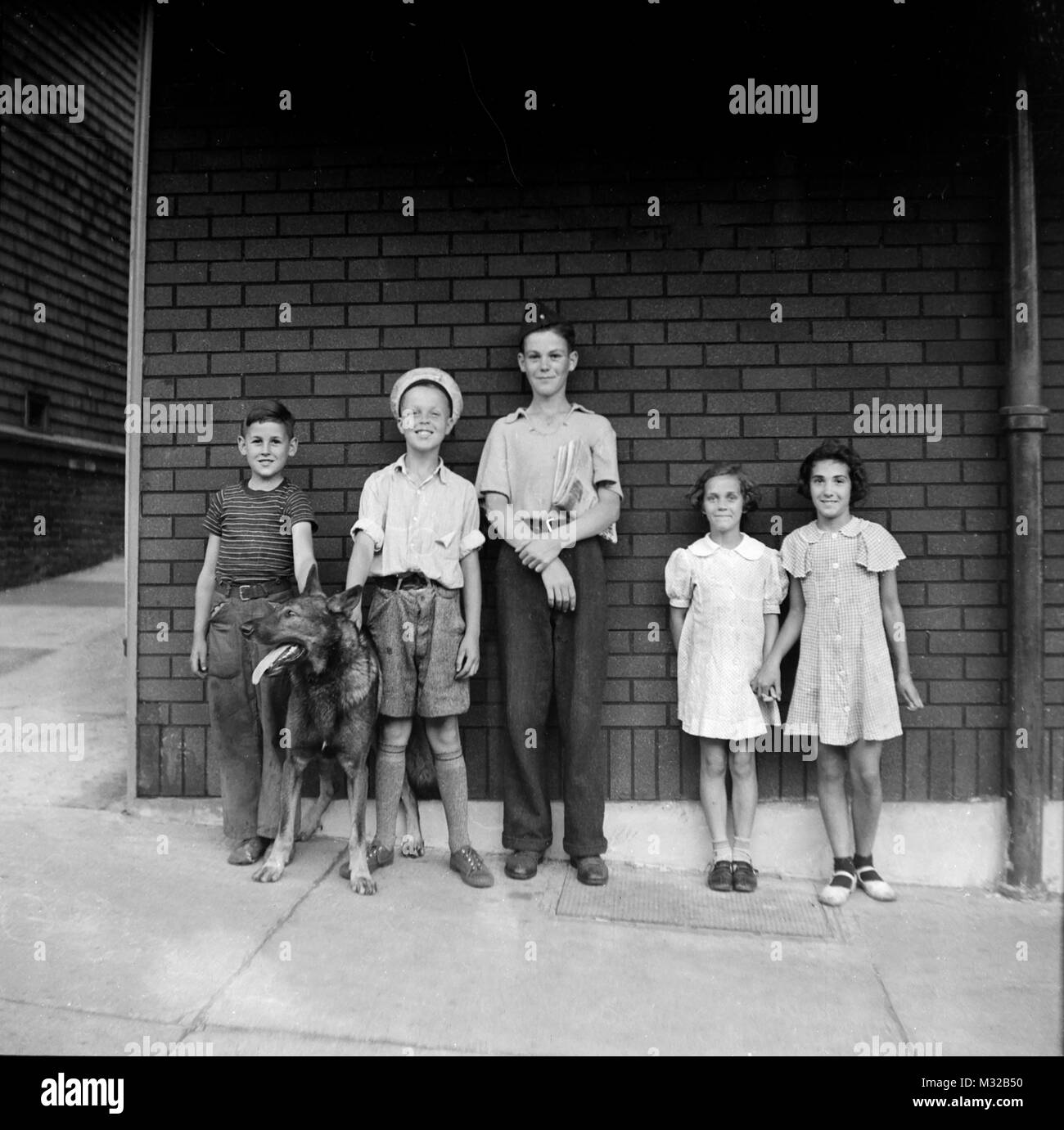 Neighborhood children and a dog line up for a photo against a brick wall, ca. 1928. - Stock Image