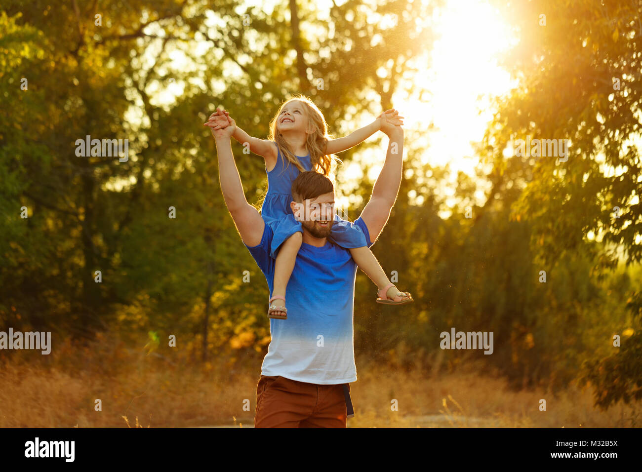 Family time. The father holds the daughter on the shoulders of piggyback. Walk in the park at sunset. They laugh - Stock Image