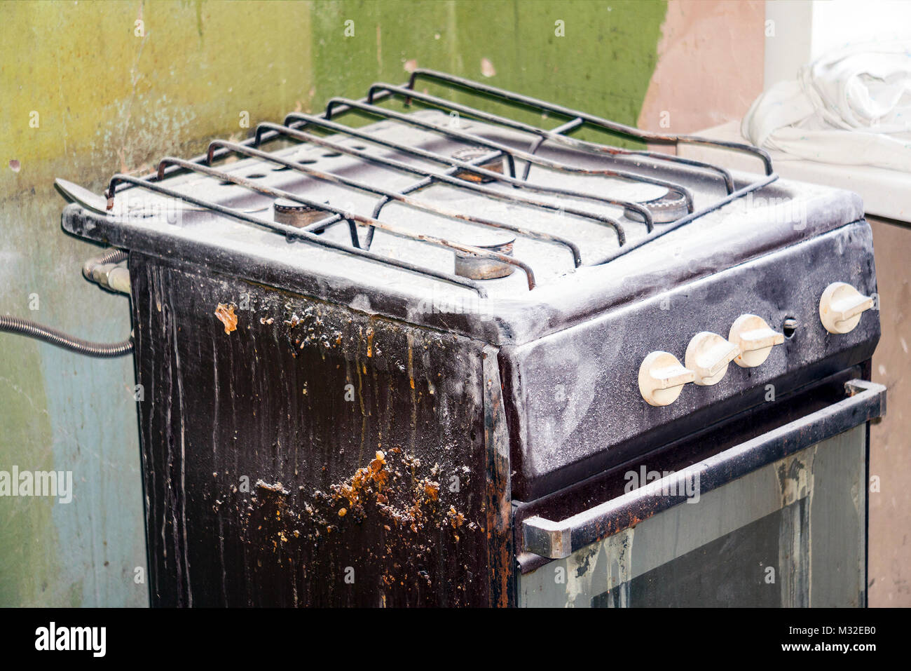 An old dirty gas stove in an abandoned state. Unsanitary conditions - Stock Image