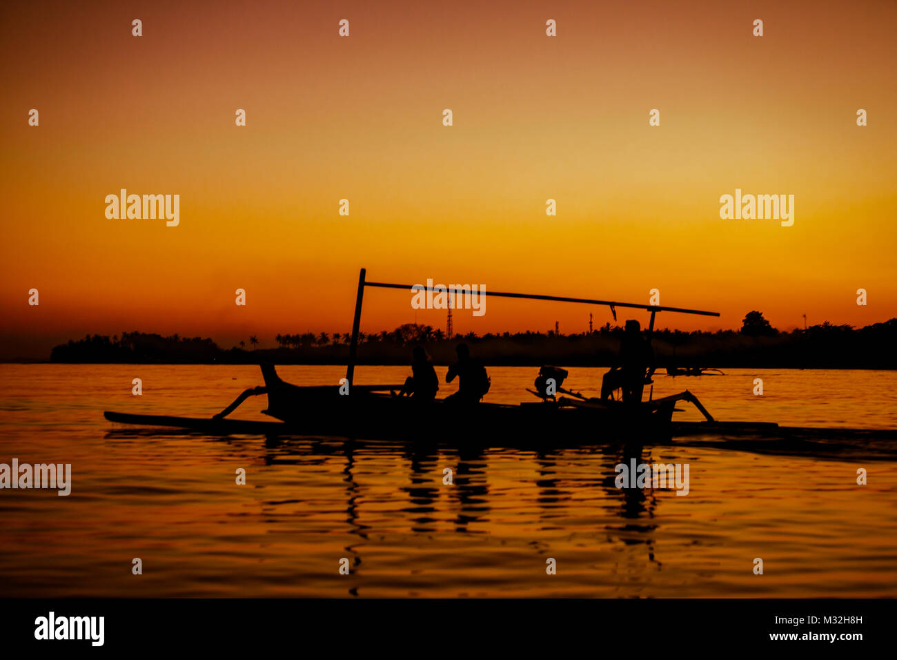 Silhouette of boat with people sailing in the early morning in Bali, Indonesia Stock Photo