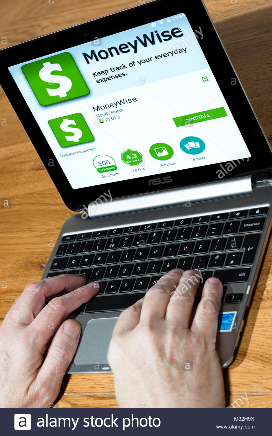Moneywise app on a Chromebook screen with a man using the keyboard on a desk, Dorset, England. - Stock Image