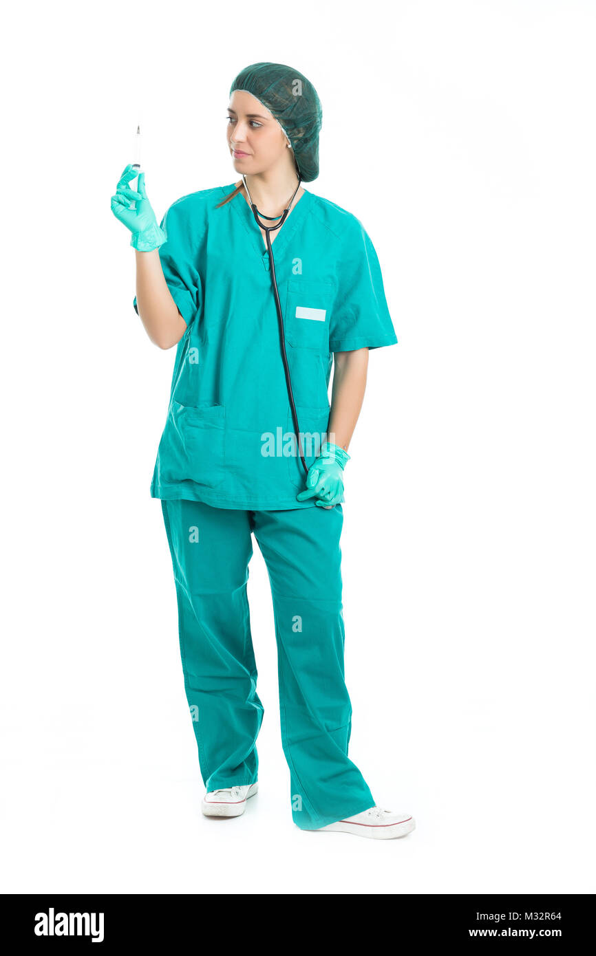 Young nurse with stethoscope standing and looking syringe in hand isolated . - Stock Image