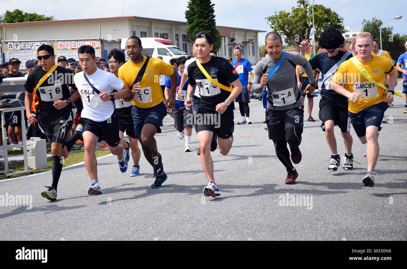 Sailors from from Naval Mobile Construction Battalion (NMCB) 1 Detail Okinawa participate in the Ekiden Relay Race - Stock Image