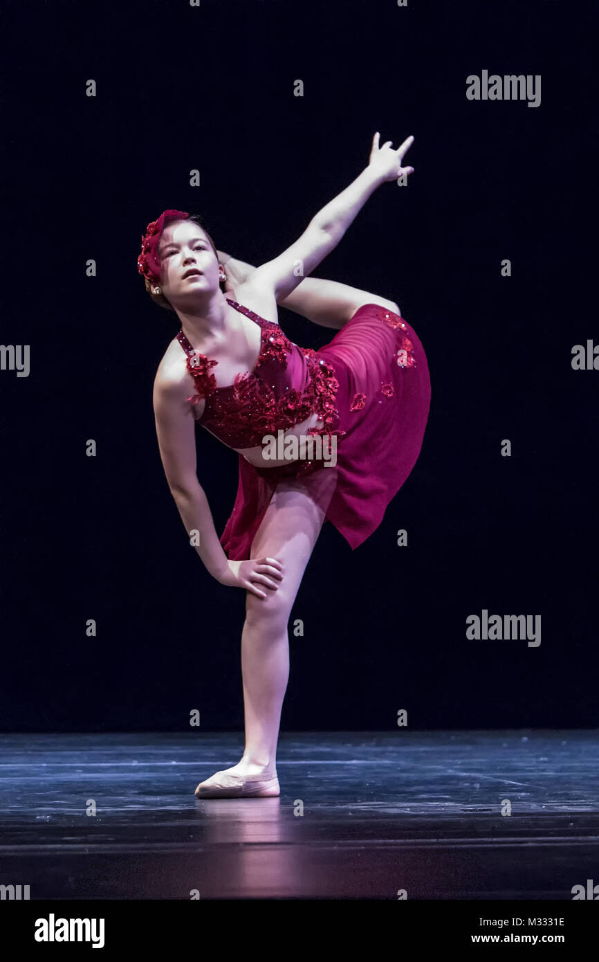 Twelve year old girl performing a solo lyrical dance onstage, doing an attitude arabesque turn - Stock Image