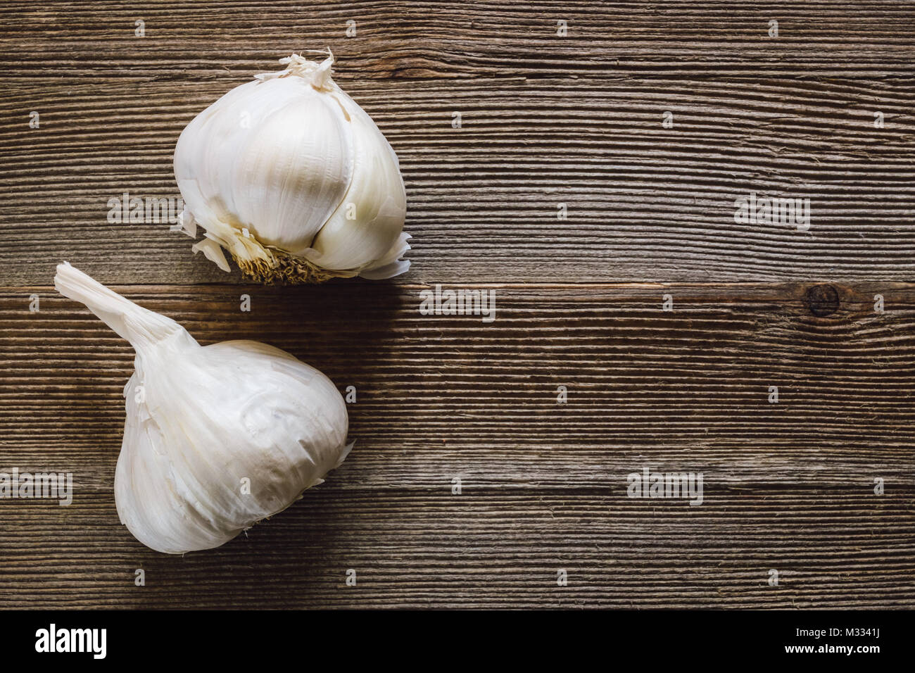 Heads of Garlic on Rustic Wooden Table with Room for Copy Stock Photo