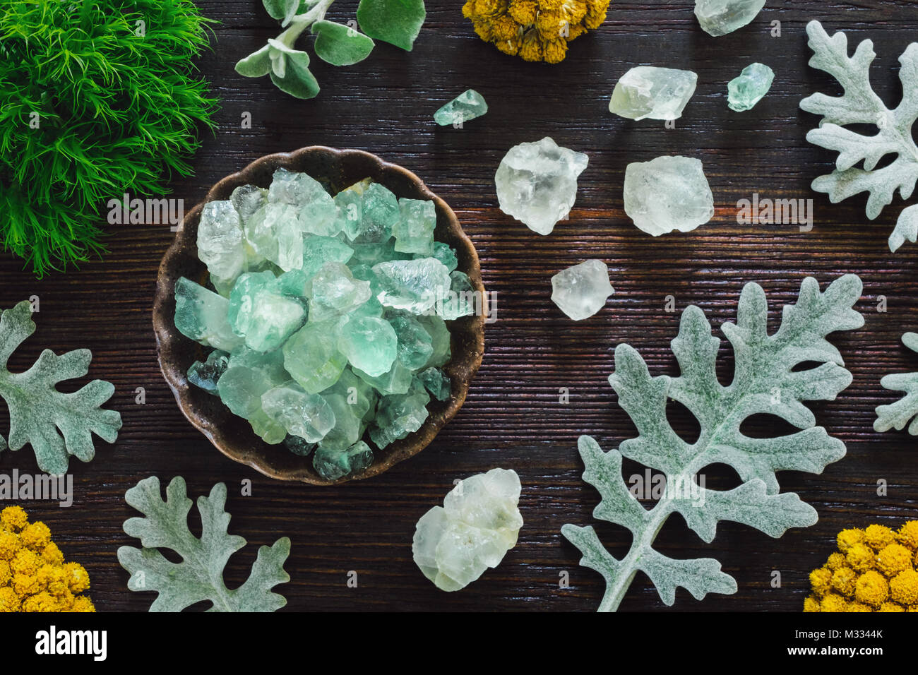 Fluorite Crystals with Dusty Miller on Dark Wood Table Stock Photo