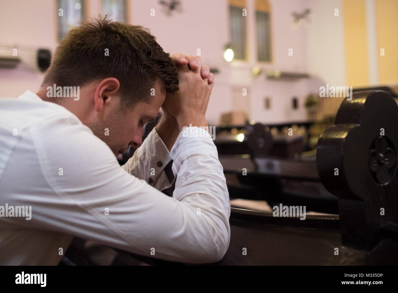 caucasian man praying in church  He has problems and ask God