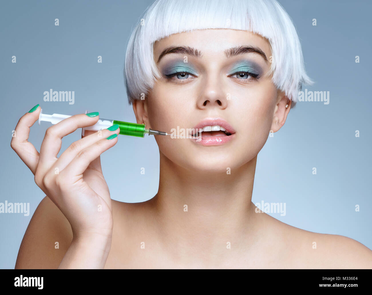 Beautiful woman face with syringe makes cosmetic injection in the lips. Clean Beauty concept - Stock Image