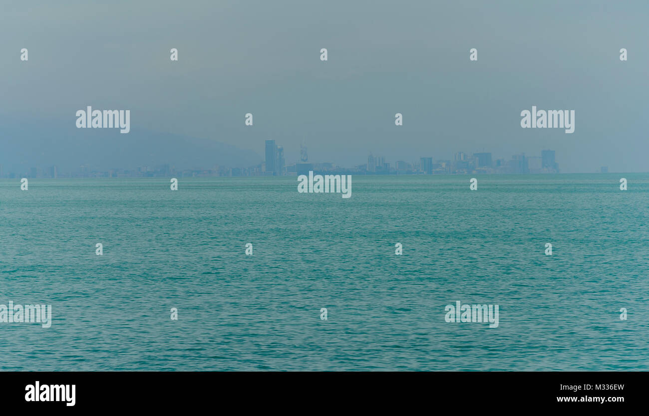 Fishing boat in foreground with fogy sea and city skyline in the background. - Stock Image