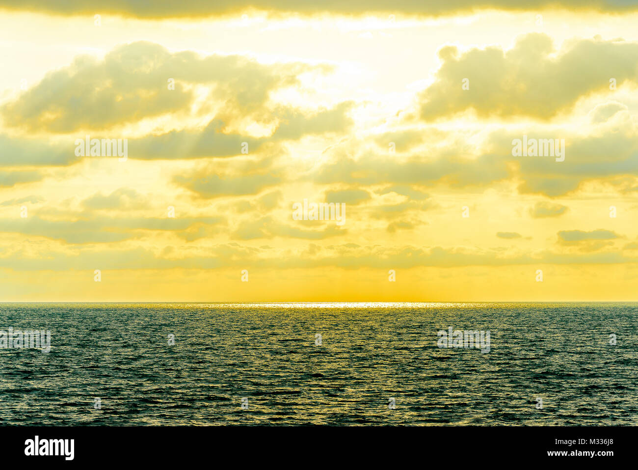 Stylized abstract landscape seascape sunset long exposure with clouds under different shades of blue, orange, yellow - Stock Image