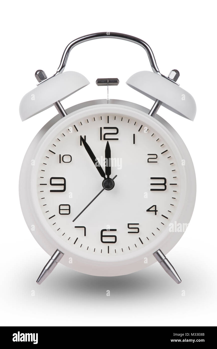 White alarm clock with the hands at 5 minutes till 12. Illustrating Time is Running Out isolated on a white background - Stock Image