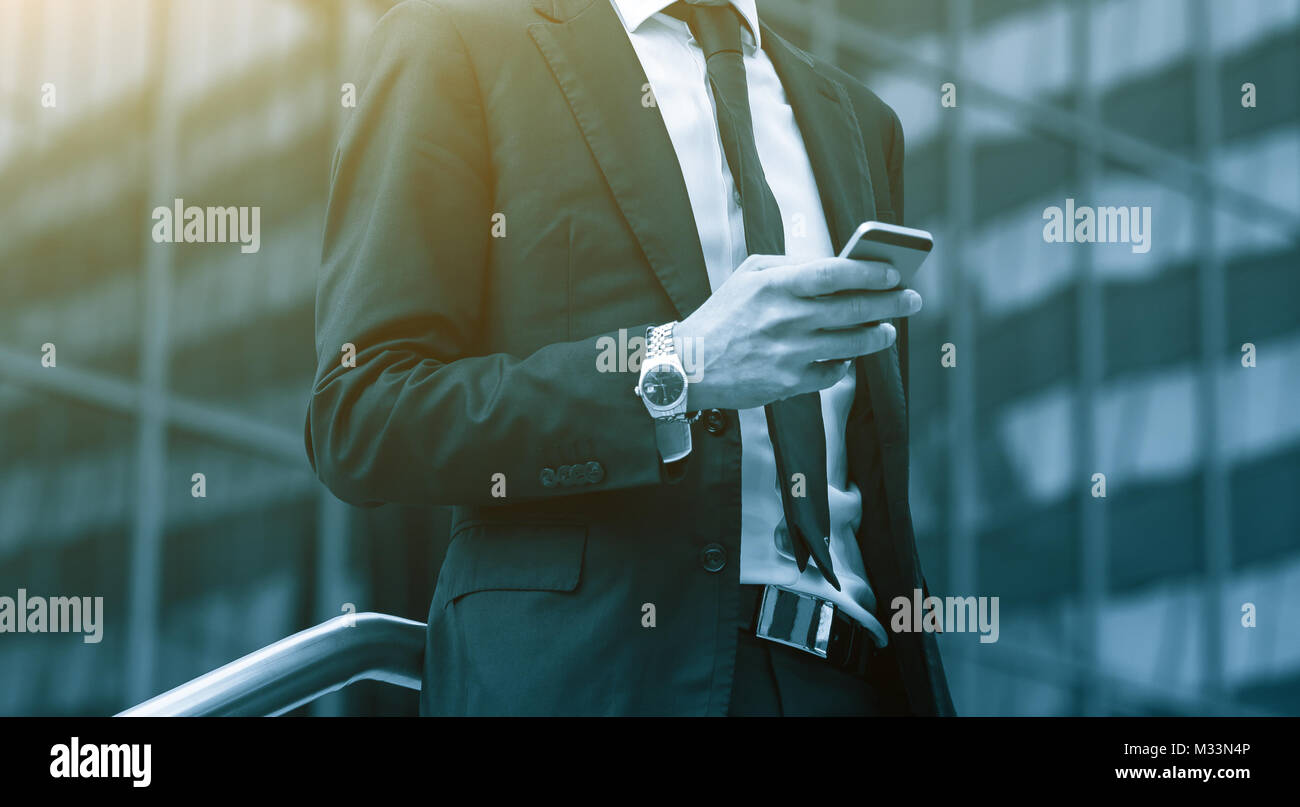Success business man using cell phone. Blue Toned Image. - Stock Image