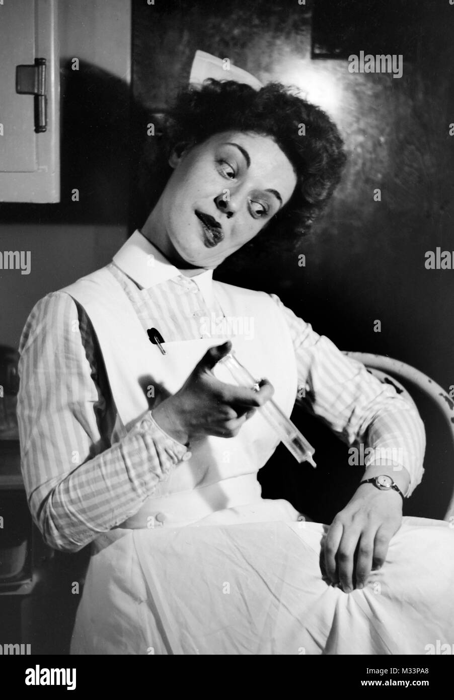 A goofy looking nurse playfully inoculates herself for humour, ca. 1910. Stock Photo