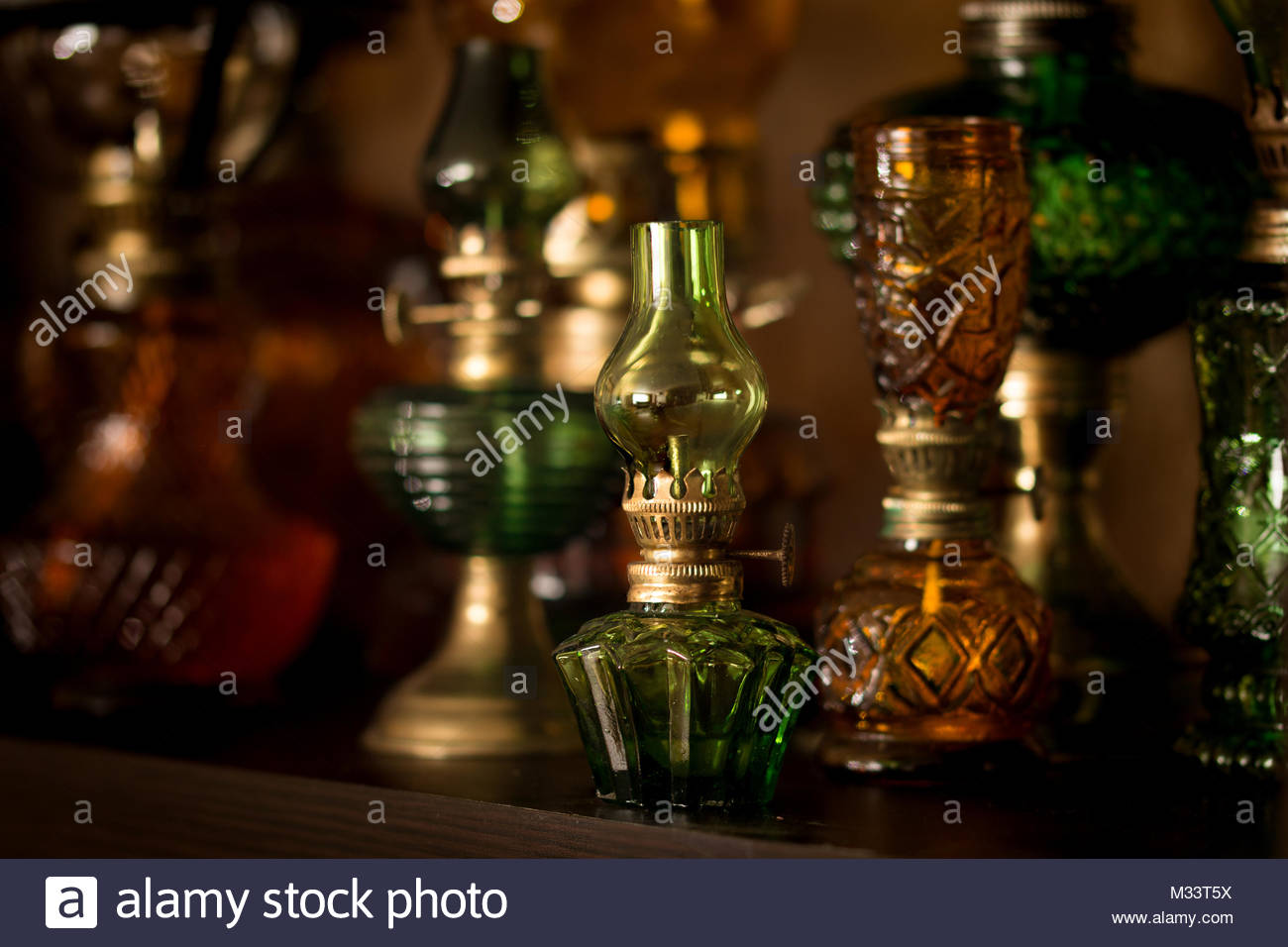 Small green kerosene lamp on background of other lamps - Stock Image