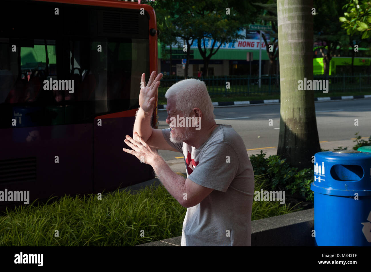 21.12.2017, Singapore, Republic of Singapore, Asia - A man is seen shielding his face from the low sun in Singapore's - Stock Image