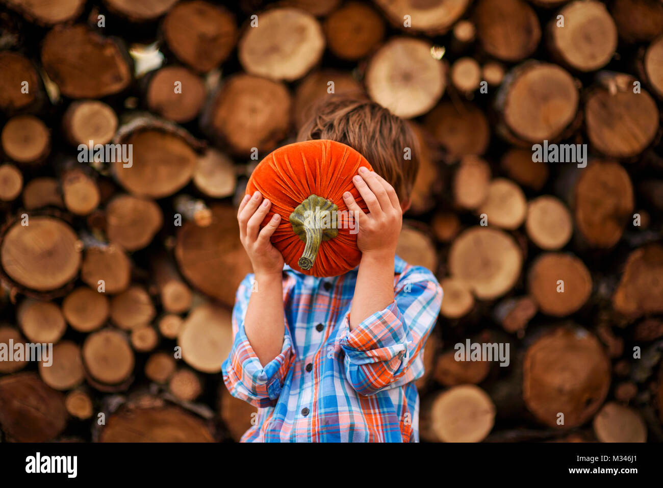 Boy holding a pumpkin in front of his face Stock Photo