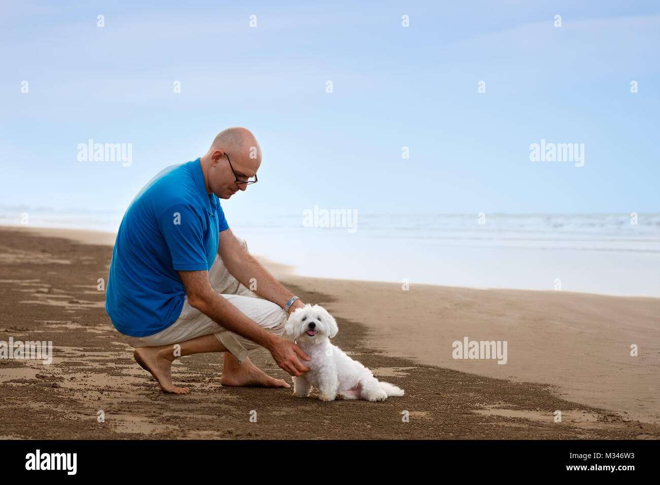 Owner looking to his dog at the beach - Stock Image