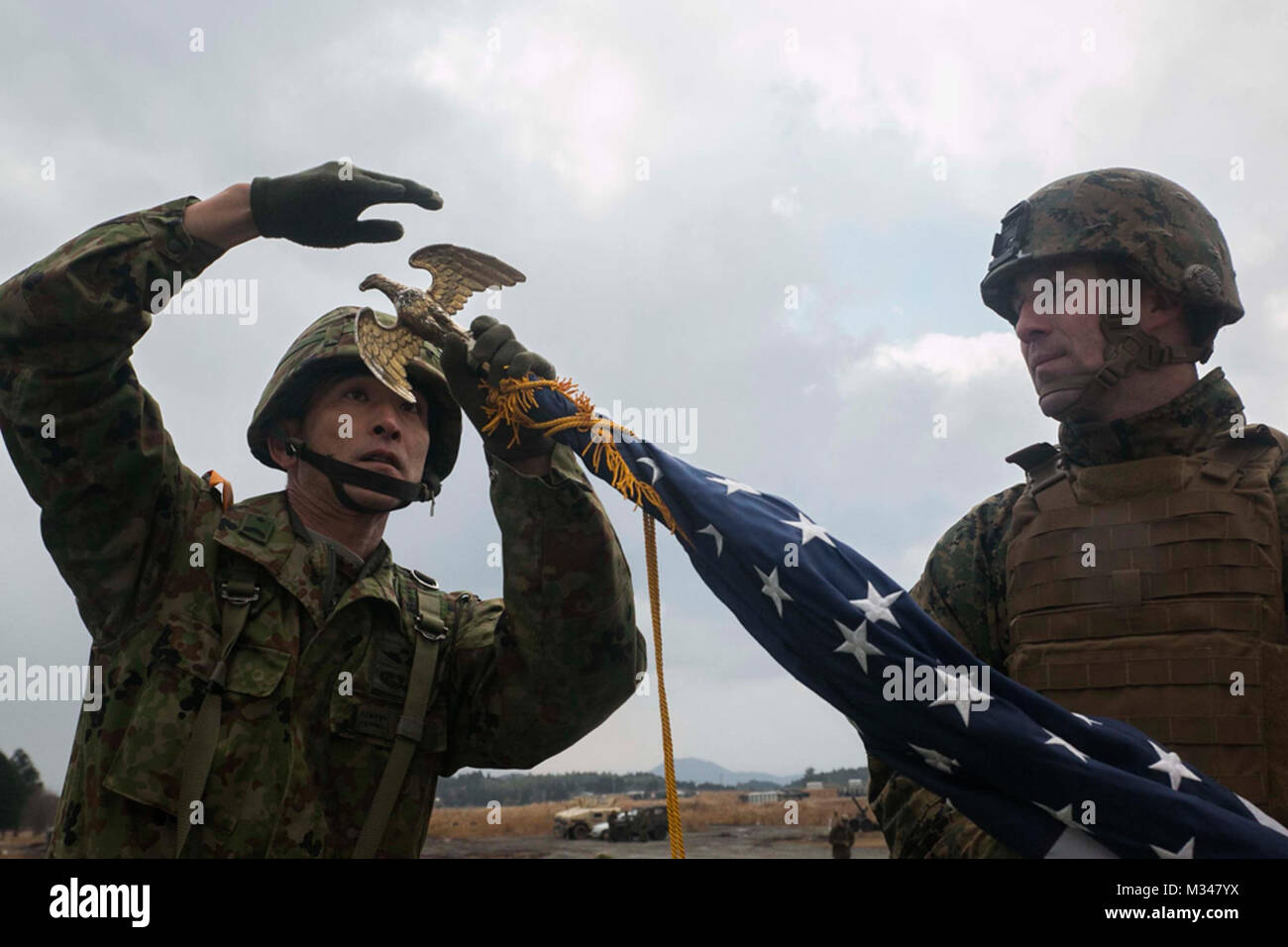 Japan Ground Self-Defense Force Sgt. 1st Class Yatsuka Ikeda, left, helps U.S. Marine 1st Sgt. Timothy Babcock set Stock Photo