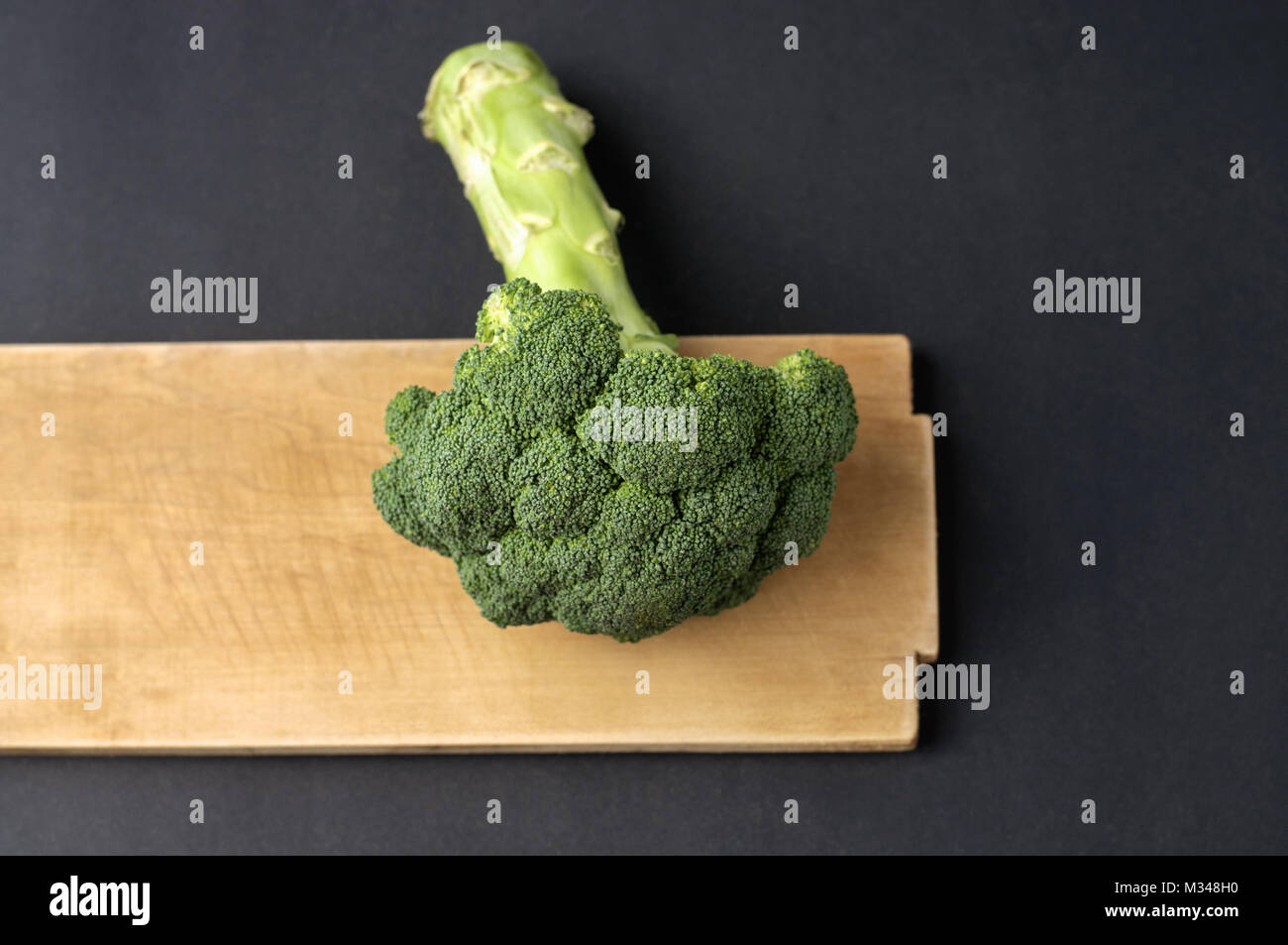 Broccoli and cutting board on dark background Stock Photo