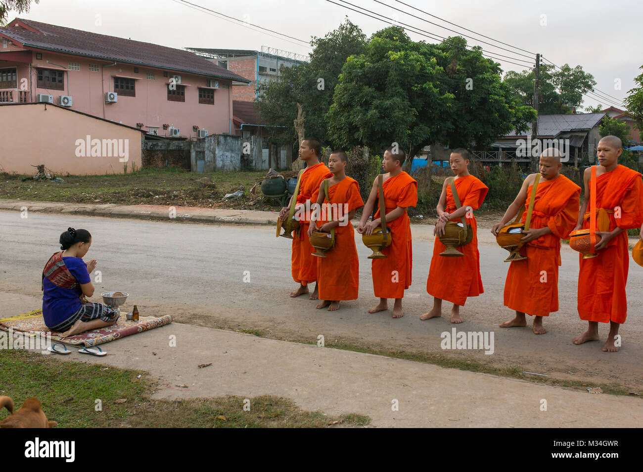 Vang Vieng, Laos - January 21, 2017: Buddhist monks collecting alms in the morning in Vang Vieng, Laos Stock Photo