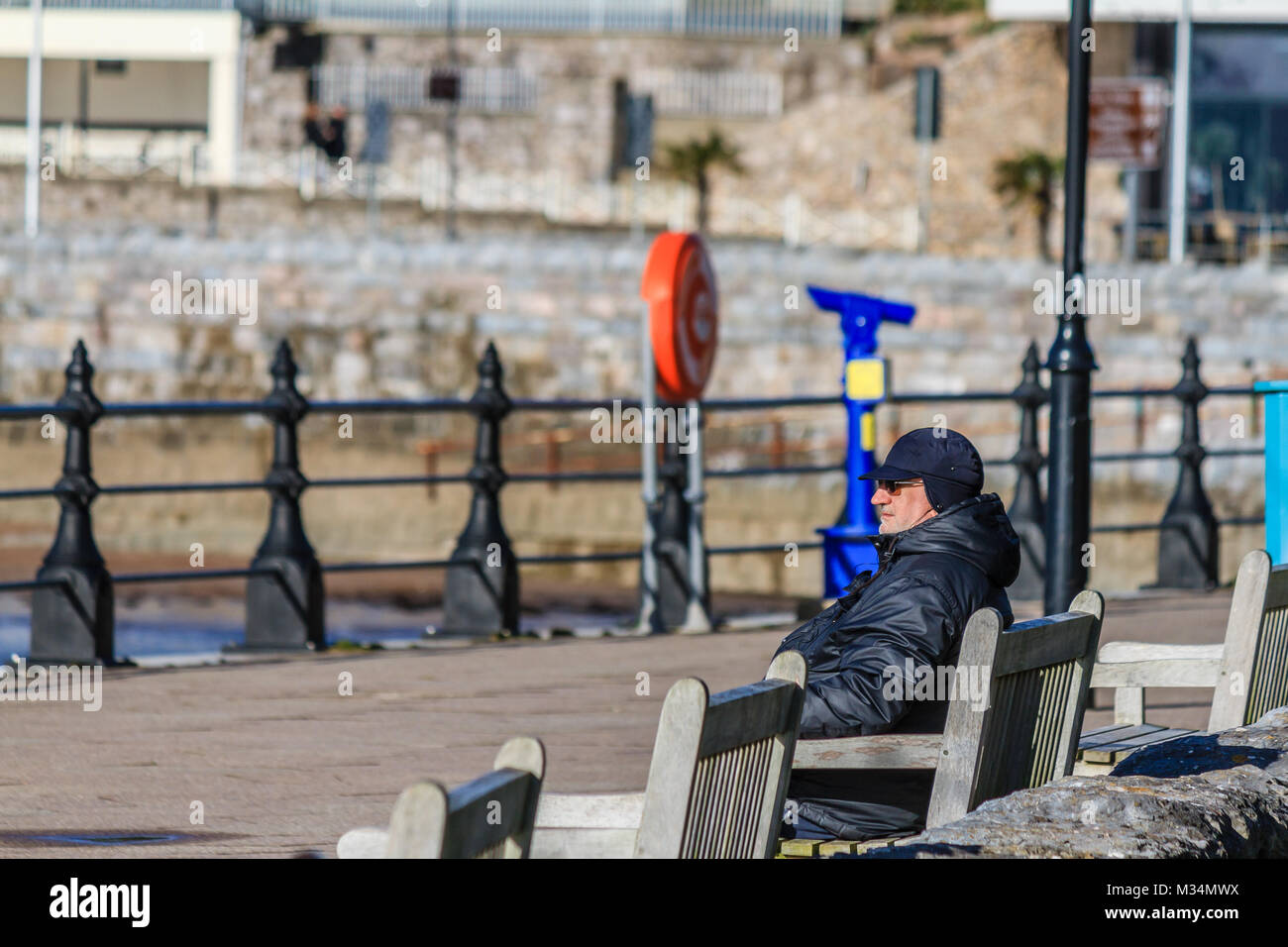 Older man sat on bench on Torquay promenade, in bright sunny but chilly weather. Torquay, Torbay, Devon, UK. February - Stock Image