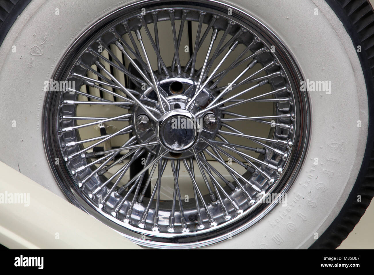close up view of a white walled tyre with steel spoked wire wheel - Stock Image